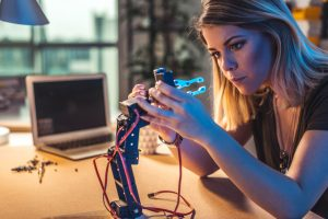 Young woman working in a robotics workshop.